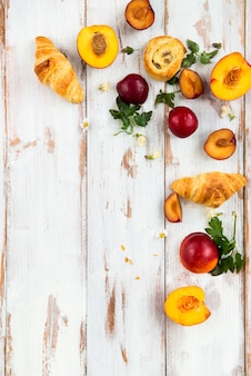 Spring or summer concept with peaches, plums, grapes and pastries