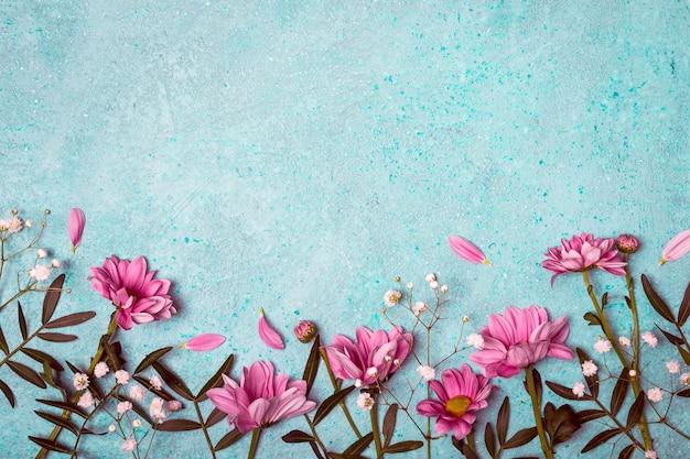 春夏クリエイティブな自然の背景。ピンクの花はヴィンテージの青い背景に隣接しています。