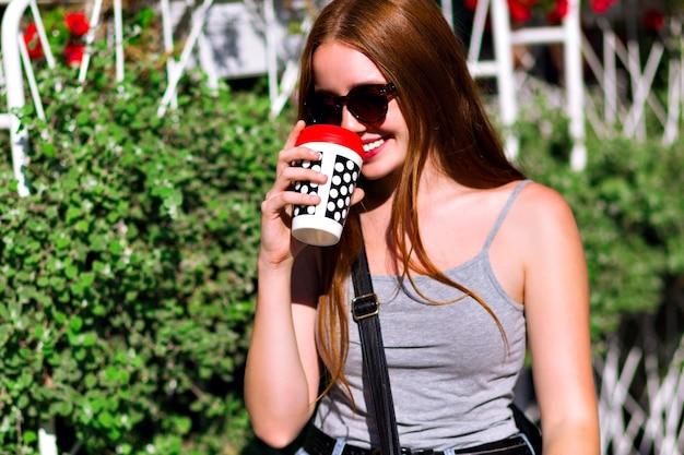 流行に敏感な若い女の子の春夏の肯定的な肖像画、ストリートスタイルのカジュアルな服を着て、市内中心部でコーヒーのテイクアウトのカップ、素晴らしい生姜の長い髪、おいしい飲み物で歩いています。