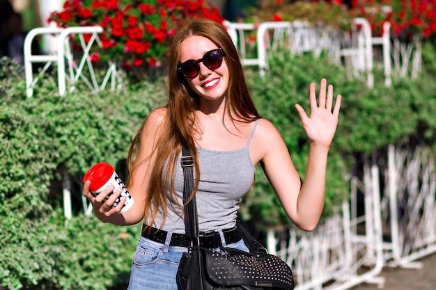 Ritratto positivo di primavera estate di giovane ragazza hipster, che indossa abiti casual in stile street, cammina in centro città con una tazza di caffè da asporto, incredibili capelli lunghi allo zenzero naturale, bevanda gustosa.