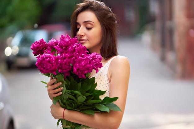 Стиль весна / лето. красивая молодая брюнетка в красивом весеннем платье с букетом пионов. красивая весенняя улица. мода весна лето фото.