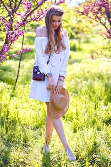 Весной солнечный модный портрет довольно белокурой женщины, позирующей в цветущем саду, в белом наряде бохо и соломенной шляпе.