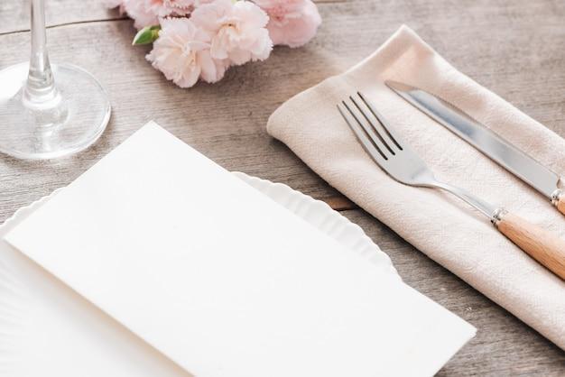 花と春のテーブルデコレーション。白いプレート、フォーク、木のプレート上のナイフ