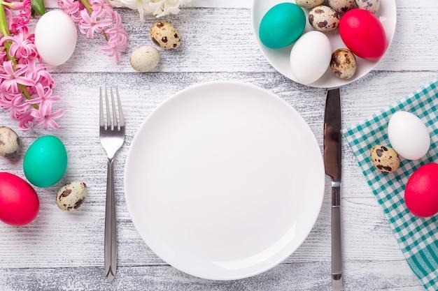 Пружинная сервировка стола. зеленая мятная тарелка, пасхальные яйца, гиацинт и серебряные столовые приборы на деревянных фоне. скопируйте пространство. вид сверху - изображение