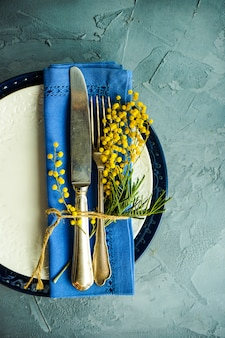 Spring table setting with mimosa flowers