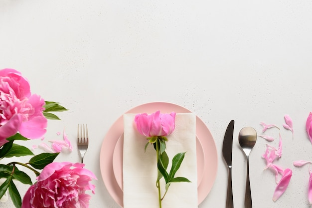 Spring table setting with pink peony flowers on a white table. view from above.