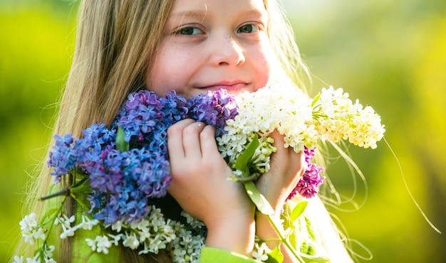 Spring teenager girl over nature green background. outdoor portraits of beautiful smiling teenager girl. teenager girl with bouquet of purple and white lilac.