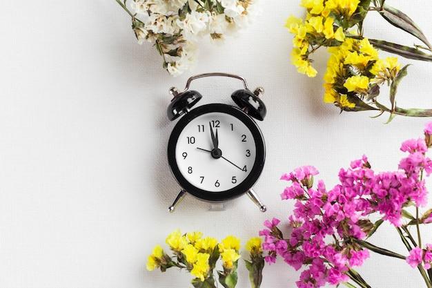 目覚まし時計と花の枝で春の時間の変更