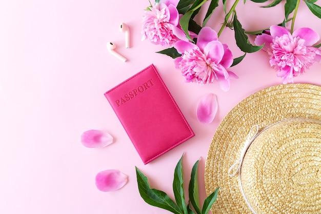 여성 액세서리가 있는 봄 여행, 휴가 및 관광:여권, 밀짚 모자, 이어폰 및 꽃