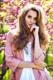 Spring trends portrait of elegant magnificent beautiful stylish woman posing near blooming trees at city garden
