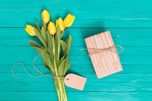 Spring tulip flowers; and gift box on green wooden table