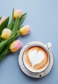 青い背景の上の春のチューリップと一杯のコーヒー