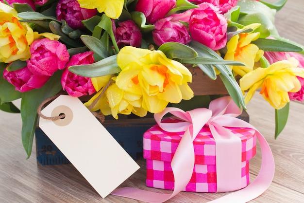 春のチューリップと水仙の花、ギフトボックスと空のタグ