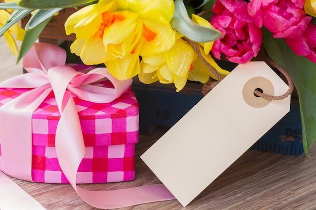 ピンクのギフトボックスと空のタグと春のチューリップと水仙の花