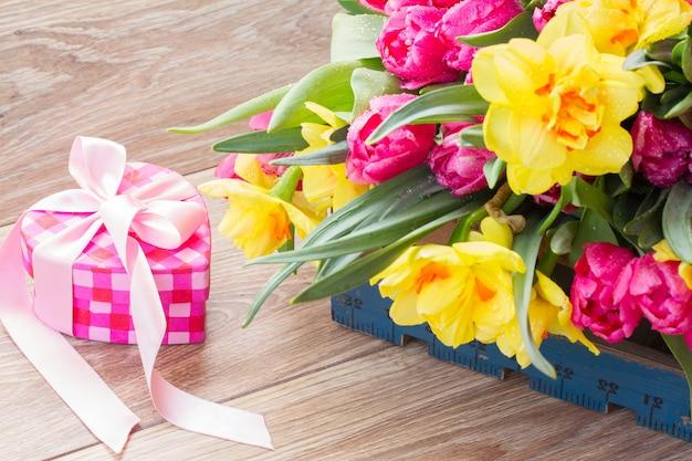 ピンクのギフトボックスと春のチューリップと水仙の花
