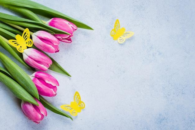 春のチューリップと母の日の背景に紙の蝶