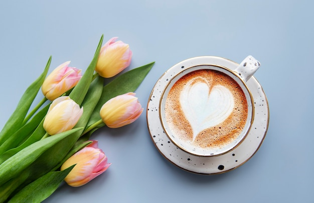 Spring tulips and cup of coffee on a blue desk