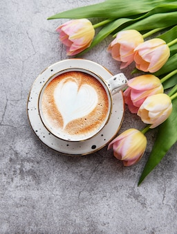 Spring tulips and cup of coffee on a concrete desk