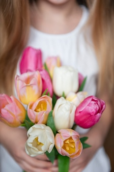 Spring tulips in the hands of a little girl.