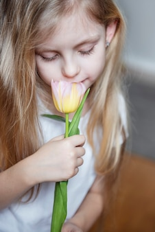 Spring tulips in the hands of a little girl