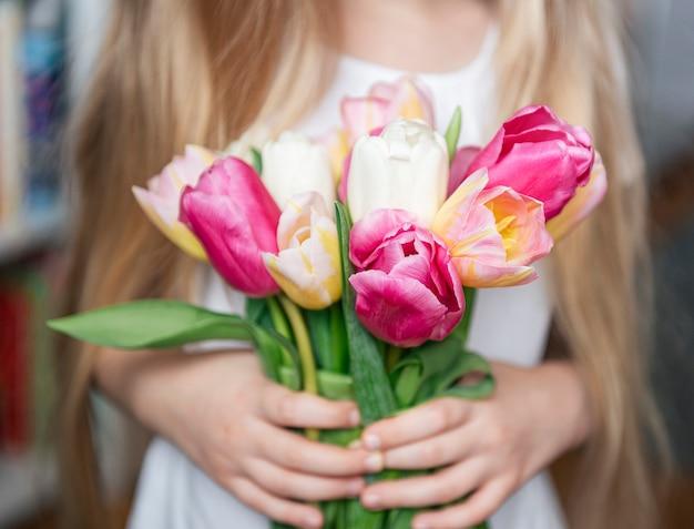Весенние тюльпаны в руках маленькой девочки. подарок ко дню матери.