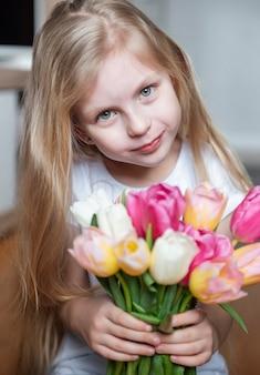 小さな女の子の手に春のチューリップ