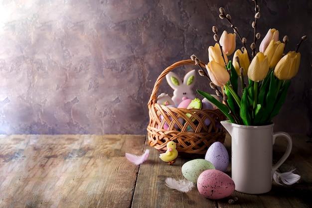 素朴な背景にイースターエッグを持つ春のチューリップ