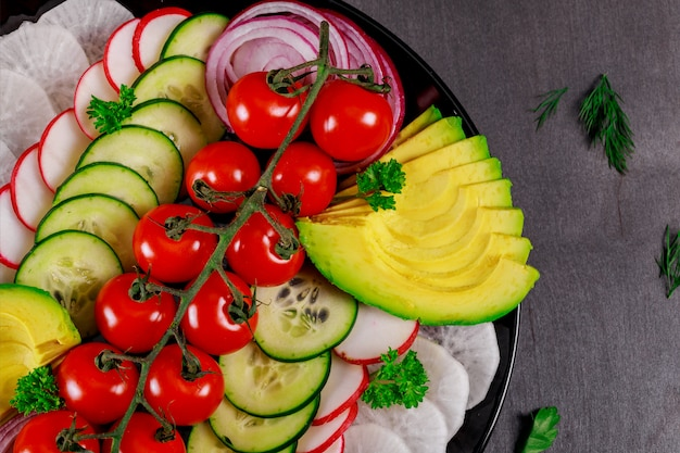 Spring vegetable salad with avocado fresh tomatoes, cucumber, onion tasty healthy food