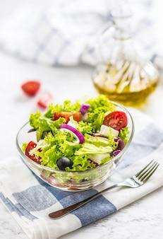 Весенний овощной салат с помидорами, луком, сыром и оливками.