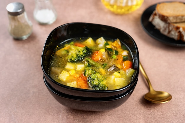 Spring vegetable soup in a black bowl