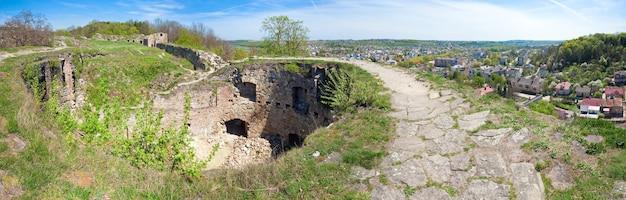 Весенний вид на развалины теребовского замка и город теребовля справа (тернопольская область, украина). построен в 1366 году. четыре кадра сшивают изображение.