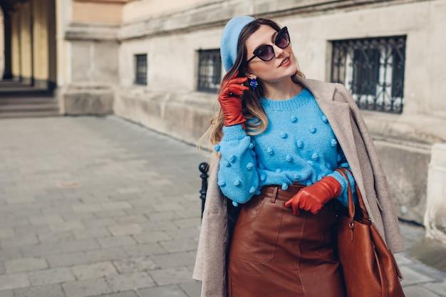 春のヴィンテージレトロなファッションの女性のアクセサリーや服。女性は路上でベレー帽の革のスカートを着ています。