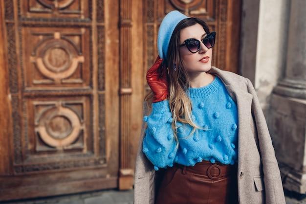 春のヴィンテージレトロなファッションの女性のアクセサリーや服。女性はセーターベレー帽の革のスカートを着ています。