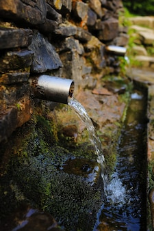 산의 숲에있는 돌담에서 금속 파이프에서 쏟아지는 샘물