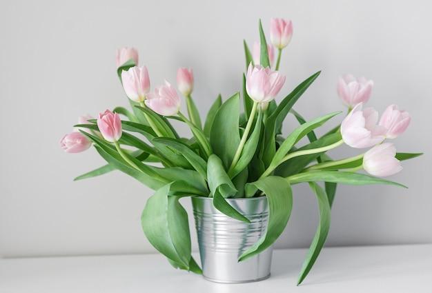Весенние белые тюльпаны в абстрактной вазе на полке, интерьер комнаты