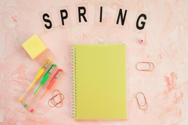 春のノートブックとペンで単語と学生デスクのワークスペース
