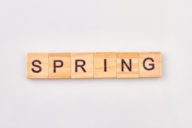 나무 블록에 쓰여진 봄 단어입니다. 흰색 배경에 고립 시즌의 개념입니다.