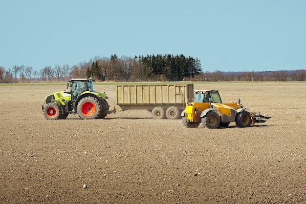 トラクターの農家で春の仕事をし、農民の土地とトラクターの種をまくためのフィールドを準備します