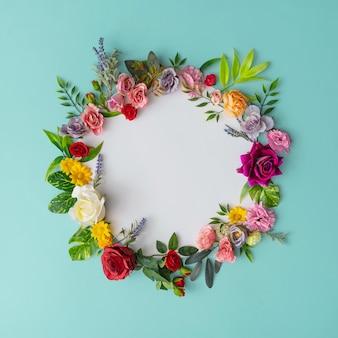 화려한 꽃과 잎으로 만든 봄 화 환. 종이 카드와 함께 자연 라운드 프레임 레이아웃.
