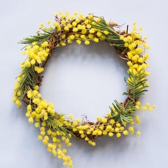青に黄色のミモザの花と春の花輪。創造的なフラットが横たわっていた。上からの眺め。