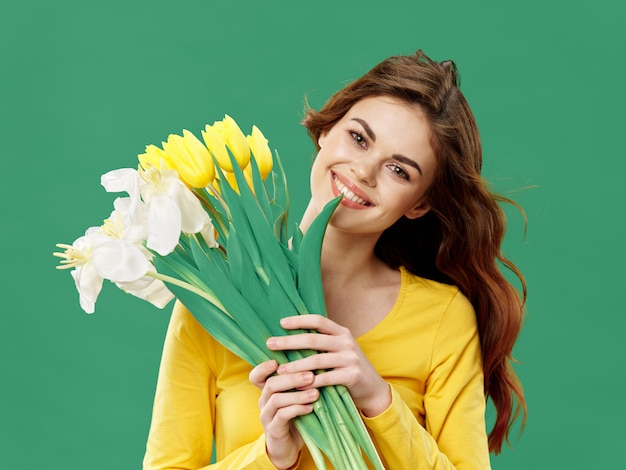 Spring young beautiful girl with flowers on a colored  space, woman posing with a bouquet of flowers, women's day