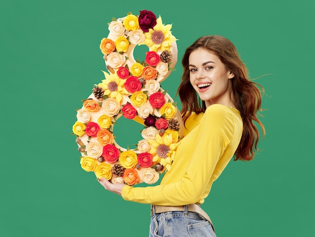 Spring young beautiful girl with flowers on a colored studio background, woman posing with a bouquet of flowers, women's day