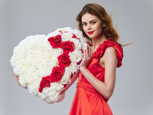 Spring young beautiful girl with flowers on a colored studio surface, woman posing with a bouquet of flowers, women's day
