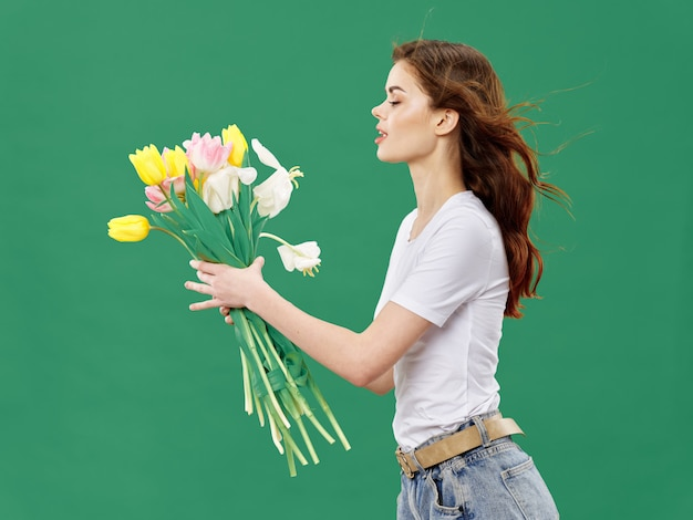 Spring young beautiful girl with flowers on a colored studio. woman posing with a bouquet of flowers.