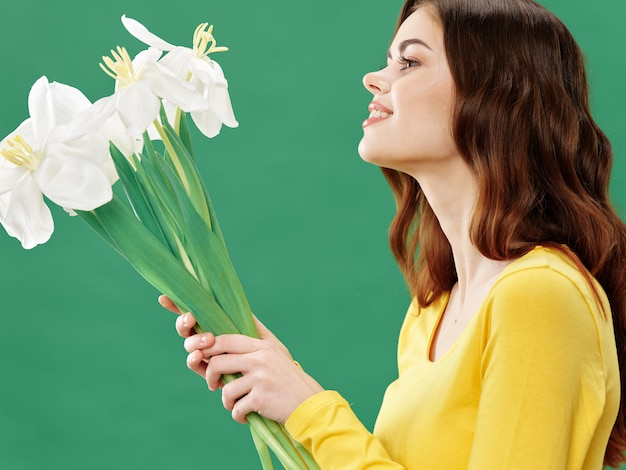 Spring young beautiful girl with flowers on a colored studio, woman posing with a bouquet of flowers