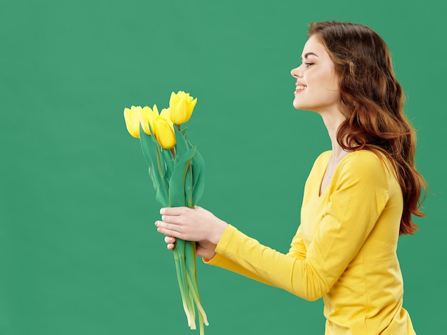 Spring young beautiful girl with flowers on a colored , woman posing with a bouquet of flowers, women's day
