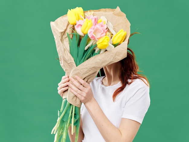Spring young beautiful girl with flowers on a colored, woman posing with a bouquet of flowers,