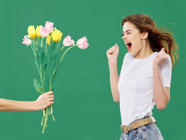 컬러 스튜디오 표면에 꽃과 함께 봄 젊은 아름 다운 소녀, 여자는 꽃의 꽃다발과 함께 포즈, 여성의 날