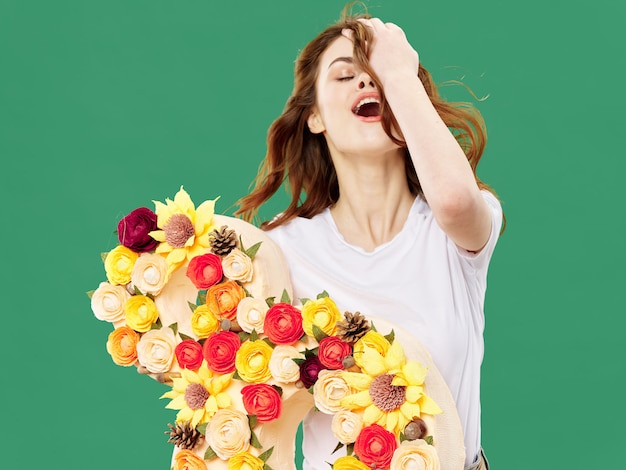 春の色のスタジオの表面に花を持つ美しい少女、女性が花の花束とポーズ