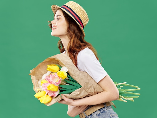 Spring young beautiful girl with flowers, woman posing with a bouquet of flowers, women's day